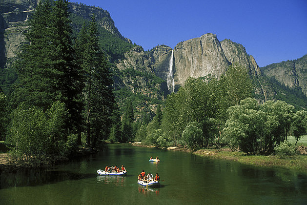 People Rafting Down Mountain River