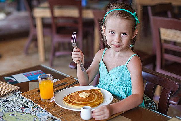 Little girl having breakfast with juice and pancake at resort restaurant