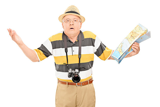 Confused mature tourist holding a map