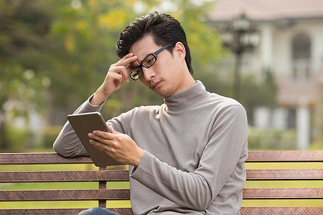 Man use tablet and thinking at park